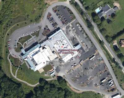 This aerial photo shows Southcoast Health Hospital in Fairhaven, Massachusetts -- a massive sea of car parking, but not a single bike rack. Image: Miles Grant